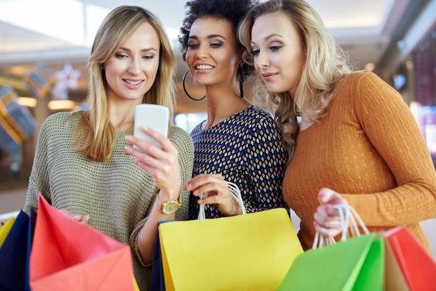 Ragazza che utilizza il suo telefono cellulare durante lo shopping Foto Gratuite