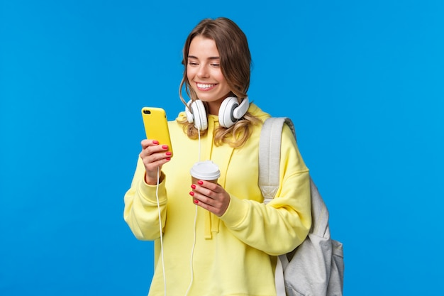 Girl using mobile phone to contact friend after college, texting as walking along street with backpack, take-away coffee cup and headphones, smiling joyfully smartphone display Premium Photo