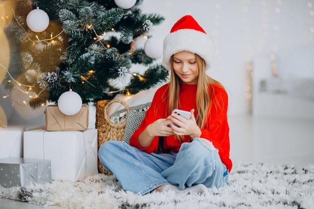クリスマスにクリスマスツリーで電話を使用して女の子 無料写真