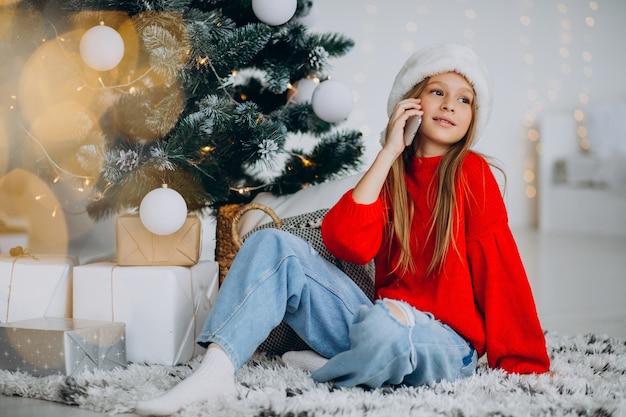 크리스마스 트리에서 전화를 사용하는 여자 무료 사진