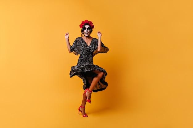 La ragazza in abito a forma di v balla e si diverte. la donna nell'immagine dello scheletro si diverte per la foto a figura intera Foto Gratuite