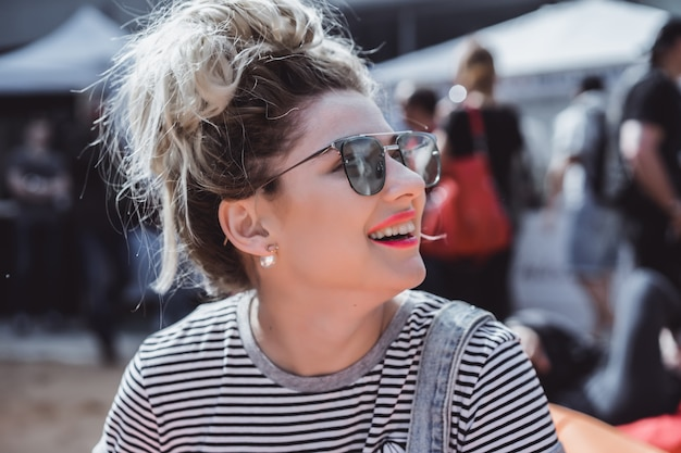 Girl in vintage sunglasses with tattoos portrait close-up on the street during a picnic with friends. chill girl Free Photo