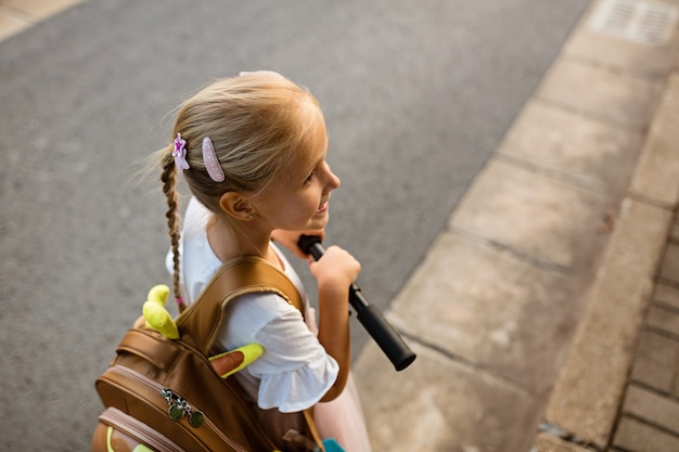 Girl walking back to home after school with schoolbag Premium Photo