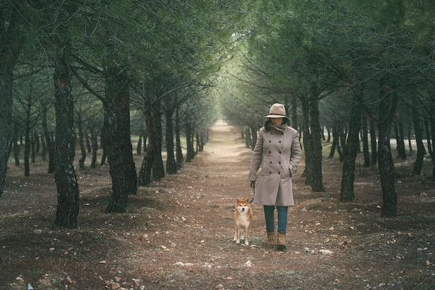 Girl walking her dog shiba inu through the field sheltered by the cold Premium Photo