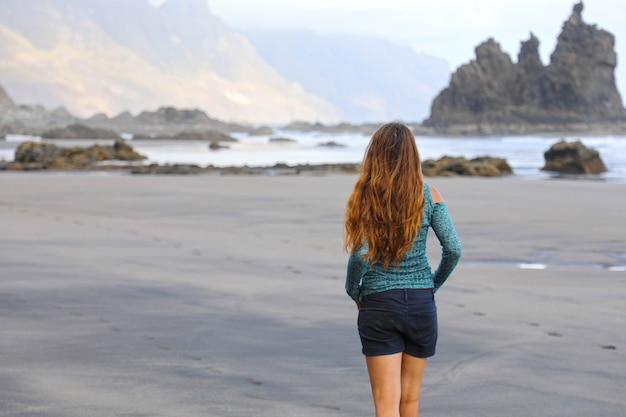 Girl walking reflexive and tranquil on hidden amazing black beach Premium Photo