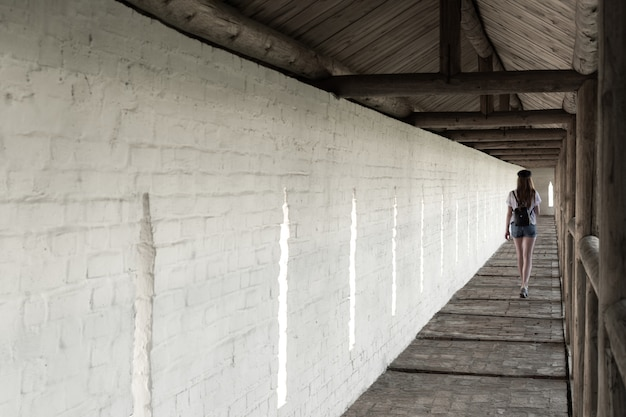 The girl walks along the long aisle of the monastery against the background of a white wall. Premium Photo