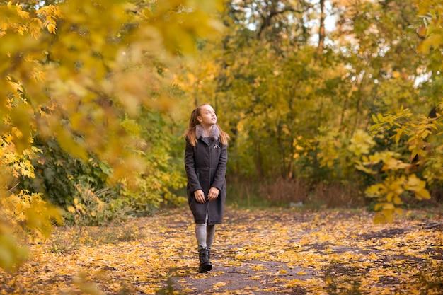 Девушка гуляет в осеннем парке ярко-желтой листвой | Премиум Фото