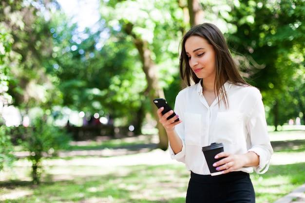 Девушка идет с телефоном в руке и чашкой кофе в парке | Бесплатно Фото