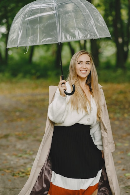 소녀가 걷는다. 갈색 코트에 여자입니다. 우산 금발. 무료 사진