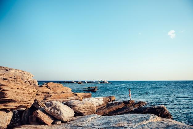 Girl wandering on the rocky beach Premium Photo