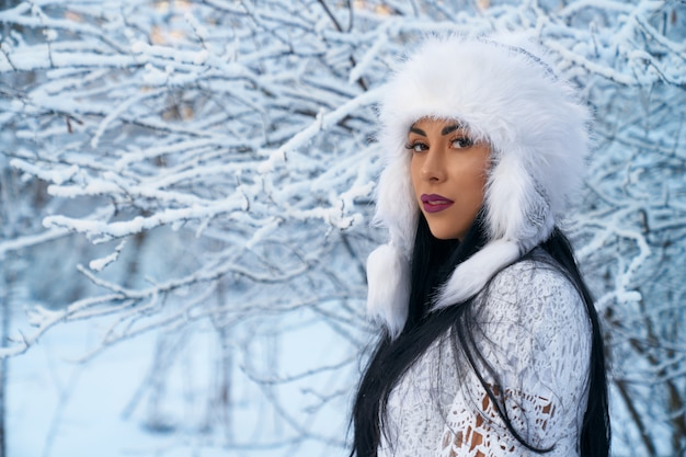 Girl in warm hat on background of trees with snow. Premium Photo