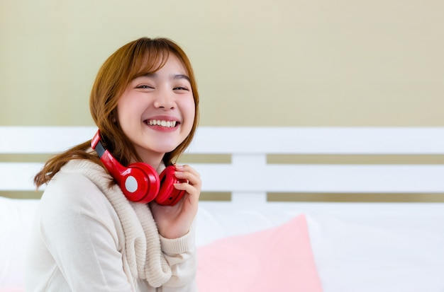 The girl was wearing headphones nd enjoying music on the bed Free Photo