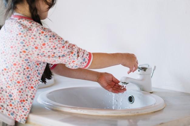 Девушка моет руку в ванной Premium Фотографии
