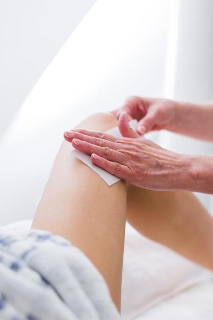 Girl waxing on her legs in a beauty salon Free Photo