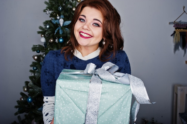 Girl wear warm sweater with christmas tree on studio with christmas box decorations at hands. happy winter holidays concept. Premium Photo