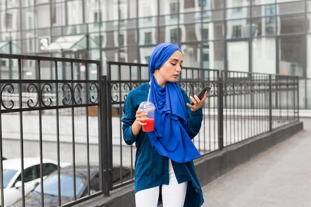 ヒジャーブを着ていると彼女の電話を見ながらスムージーを保持している女の子 無料写真