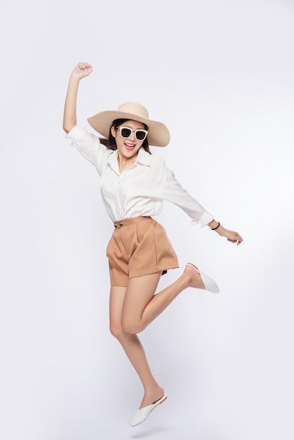 Девушка в белой рубашке и шортах, в шляпе носите очки и держите шляпу ручкой Бесплатные Фотографии