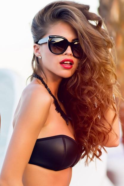 Girl wearing a bikini posing and wearing sunglasses Free Photo