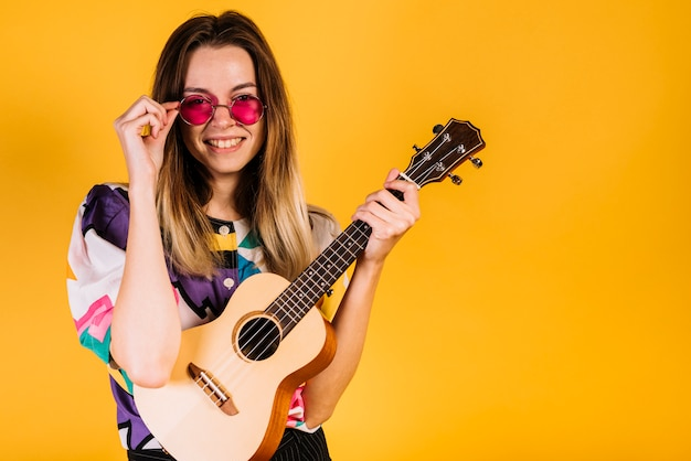 Girl wearing glasses with an ukelele Free Photo