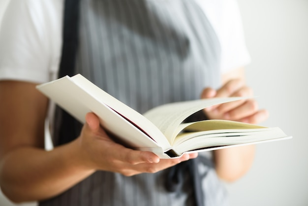 Girl wearing grey apron and reading book. lifestyle concept Premium Photo