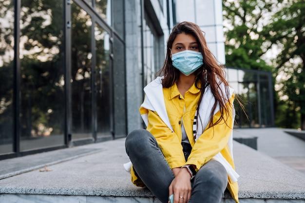 通りでポーズのマスクを着ている少女。コロナウイルス発生の検疫中の流行。 無料写真