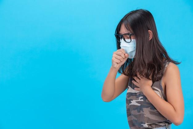 Una ragazza che indossa una maschera che mostra tosse starnuti su una parete blu Foto Gratuite