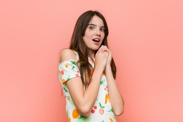 Girl wearing a summer clothes against a  wall scared and afraid. Premium Photo