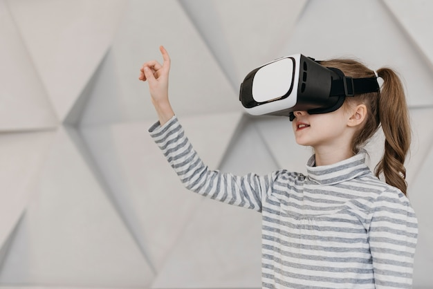 Ragazza che indossa le cuffie da realtà virtuale e tenendo la mano in aria Foto Gratuite