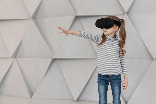 Ragazza che indossa le cuffie da realtà virtuale e allungando la mano Foto Gratuite
