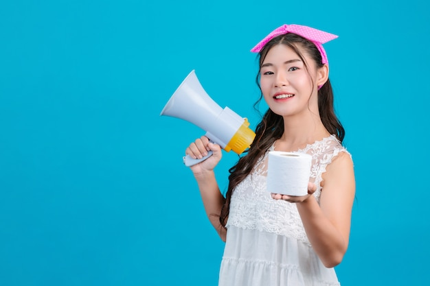 : a girl wearing a white pajamas holding a megaphone and holding tissue paper in her hand on a blue . Free Photo