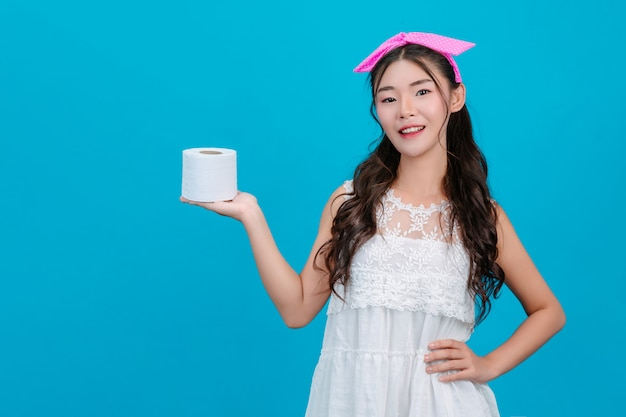 Girl wearing white pajamas holding a roll of tissue paper in the hand on the blue . Free Photo
