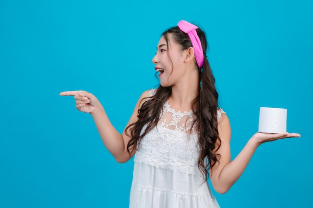 Girl wearing white pajamas holding a rolltissue paper in the hand on the blue . Free Photo