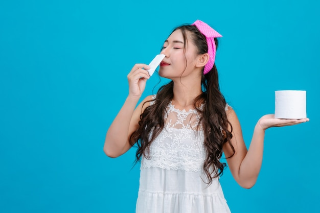 : a girl wearing a white pajamas sniffing a tissue and holding a tissue in her hand on a blue . Free Photo