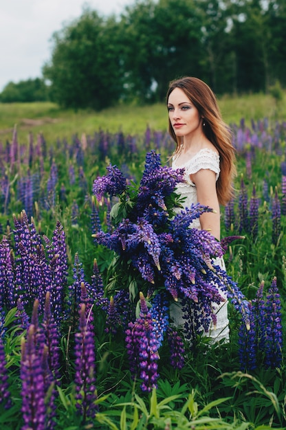 A girl in a white dress is standing among the lupines Premium Photo