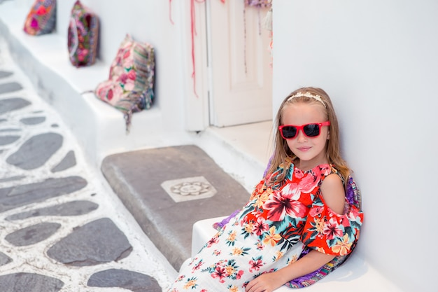 Girl in white dresses having fun outdoors on mykonos streets Premium Photo