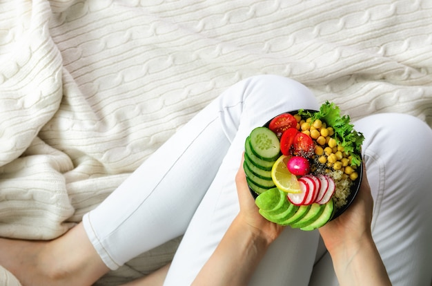 Girl in white jeans holds in hands fork, vegan breakfast meal in bowl with avocado, quinoa, cucumber, radish, salad, lemon, cherry tomatoes, chickpea Premium Photo