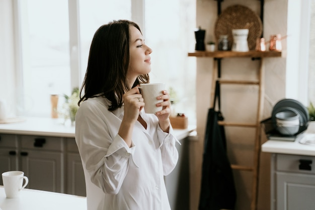 Girl in a white shirt drinks coffee in the morning in a kitchen. Premium Photo