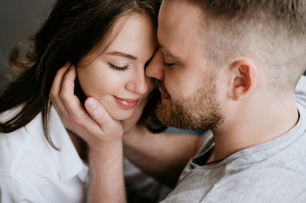 Girl in a white shirt and a guy in a gray t-shirt. kiss and hug. Premium Photo