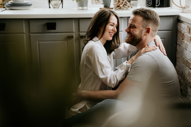 Girl in a white shirt and a guy in a gray t-shirt in the kitchen. kiss and hug. Premium Photo