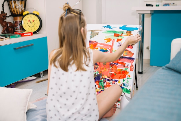 Girl in white sitting on floor and painting with gouache on canvas Free Photo