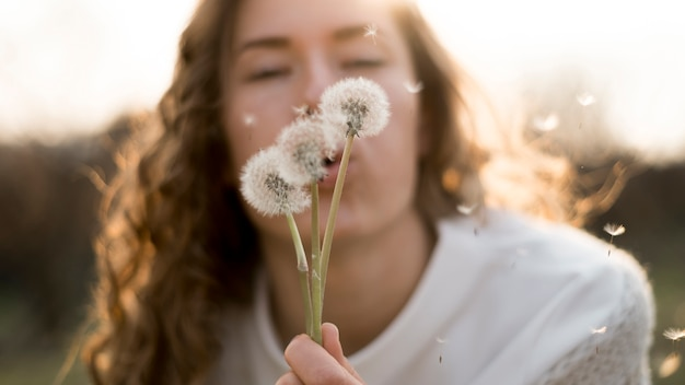 Girl in white t-shirt blowing dandelions Free Photo