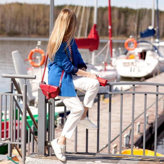 The girl in white trousers and a blue jacket looks at the sea Premium Photo
