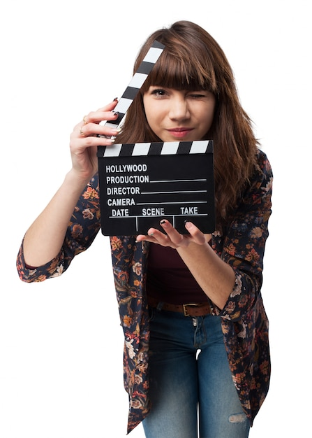 Girl winking and showing a clapperboard Free Photo