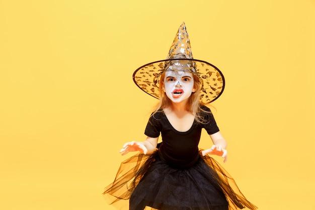 Girl in witch halloween costume Premium Photo
