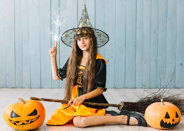 Girl in witch suit sitting on floor doing magic Free Photo