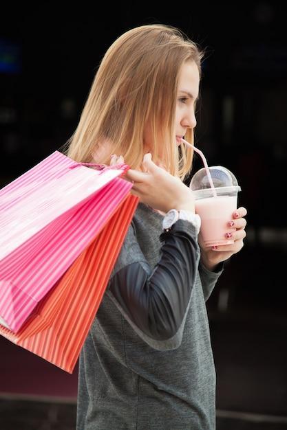 دختر با یک لیوان و کیسه های خرید