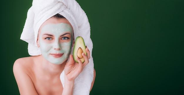 Девушка с белым полотенцем на голове с питательной зеленой маской на лице и авокадо в руках на зеленом фоне с местом для текста Premium Фотографии