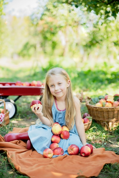 Girl with apple in the apple orchard. beautiful girl eating organic apple in the orchard. Premium Photo