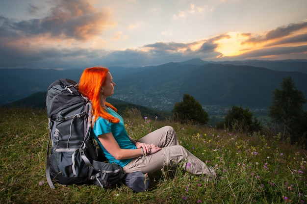Girl with backpack sitting in the grass with flowers on a hill at sunset Premium Photo