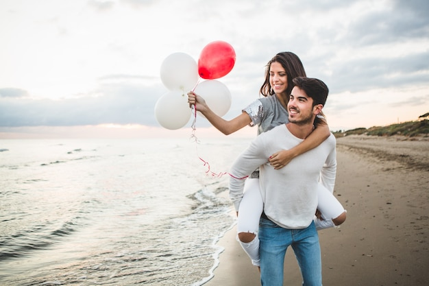 Girl with balloons while her boyfriend carries her on her back Free Photo